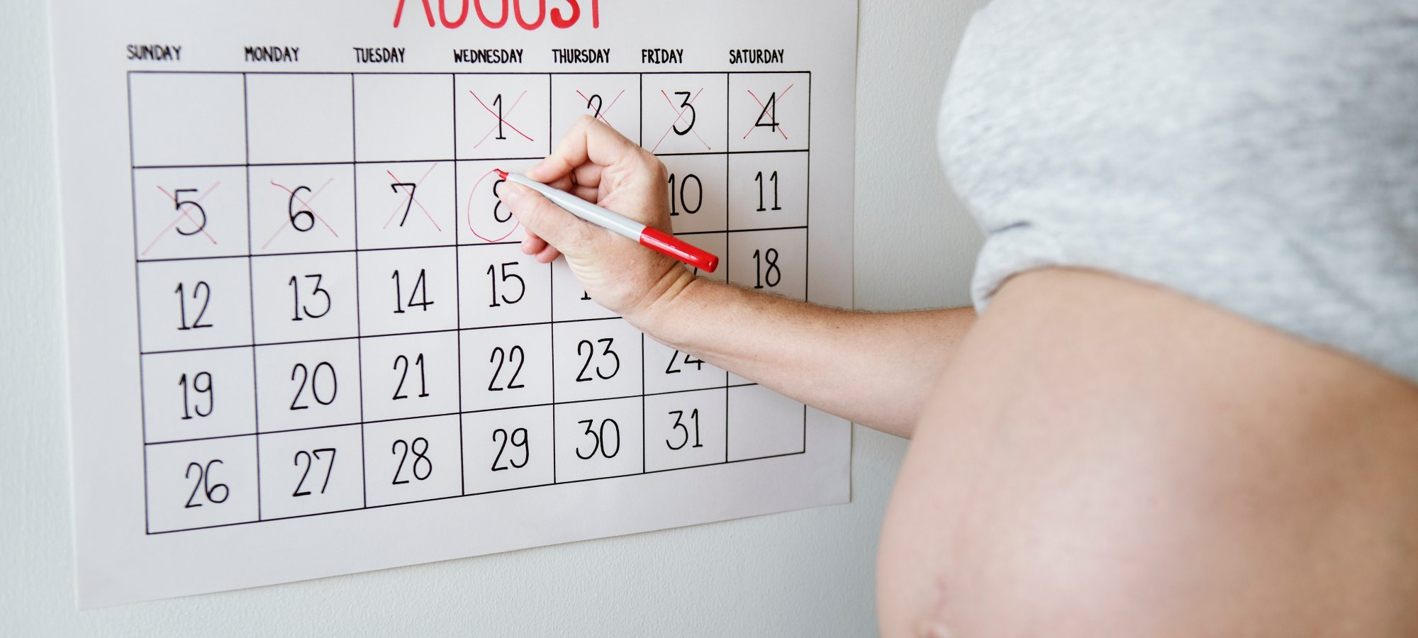 Pregnant woman writing on calendar
